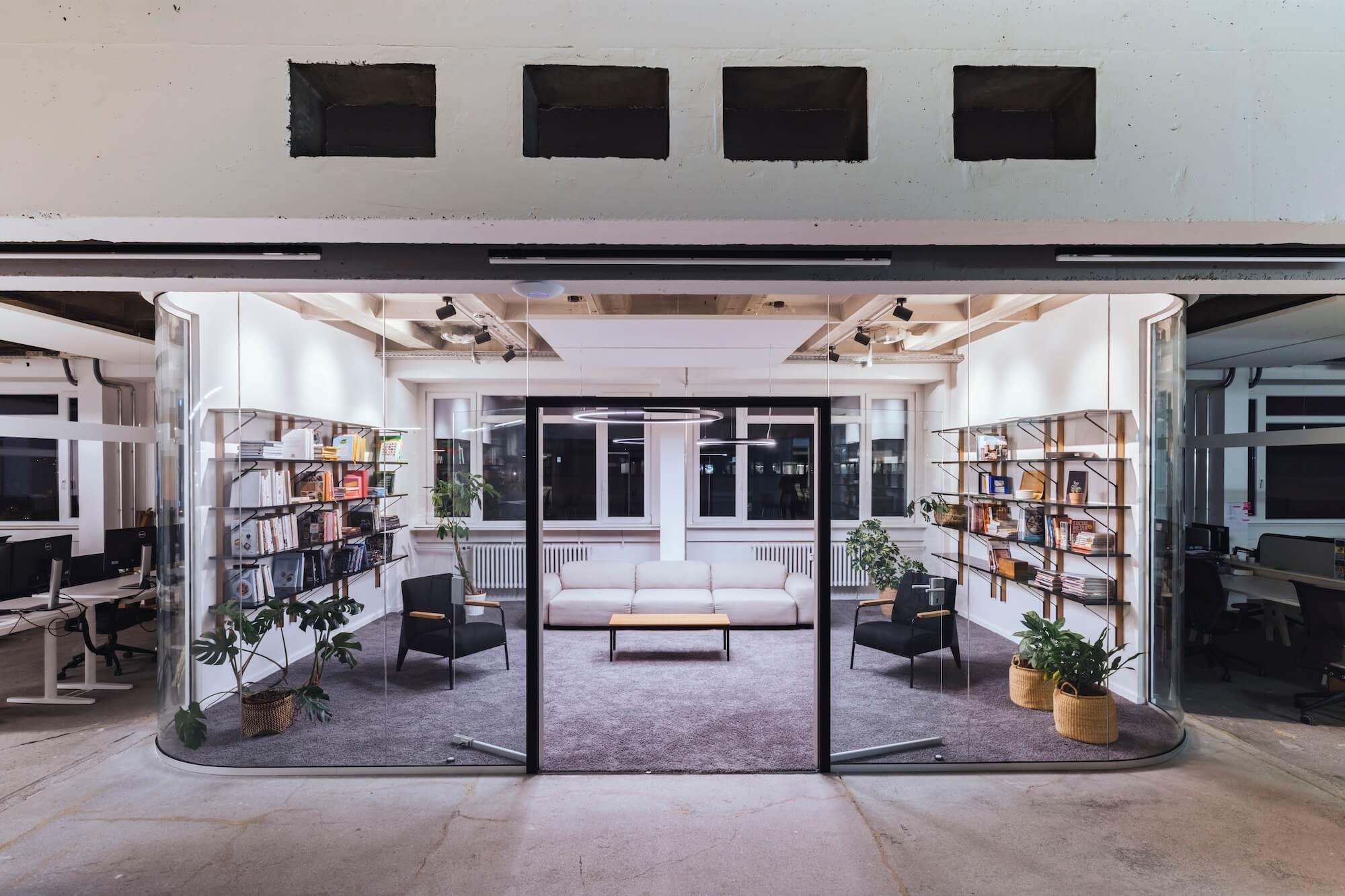 Open Space Büro Startup Kitchen Stories Architekturbüro TKEZ Bibliothek bei Nacht